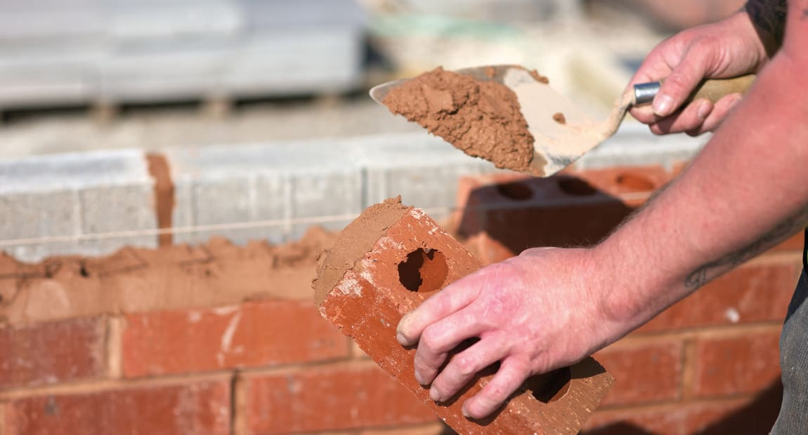 builder laying bricks to create a wall