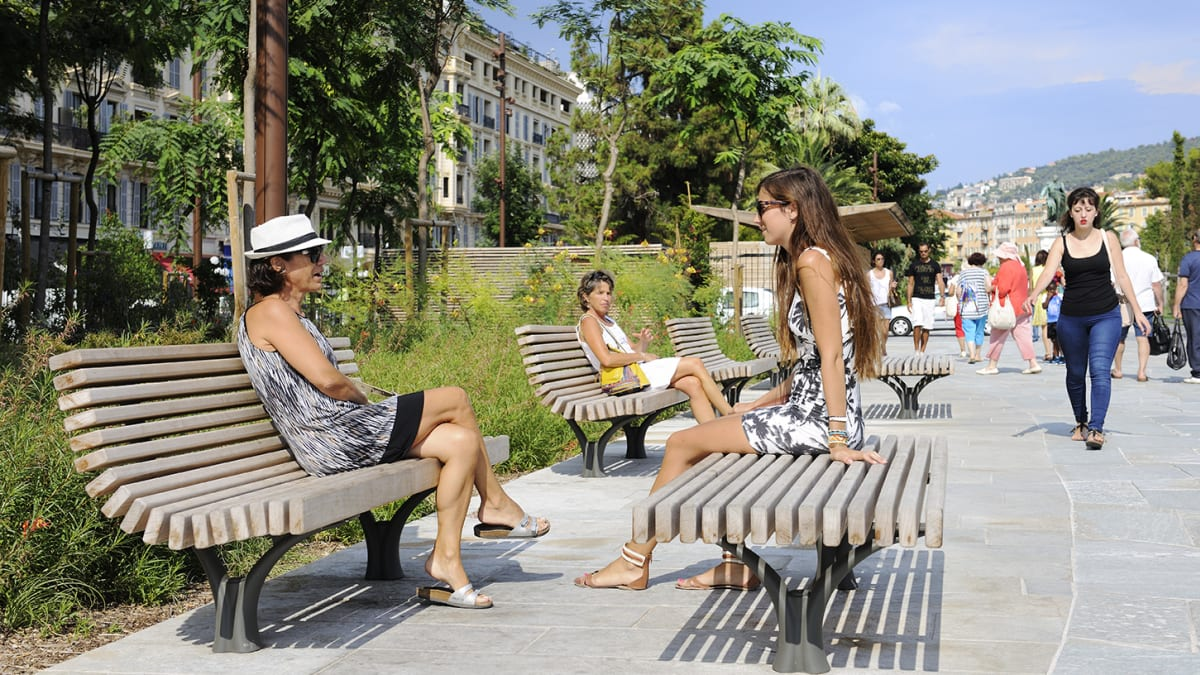 2 women sat on a wooden bench.