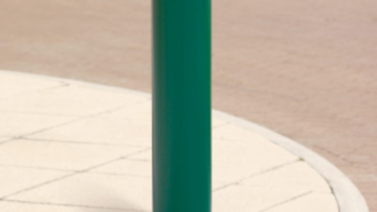 green bollard on pavement