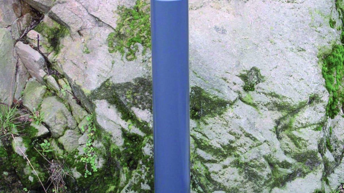blue bollard near a rock
