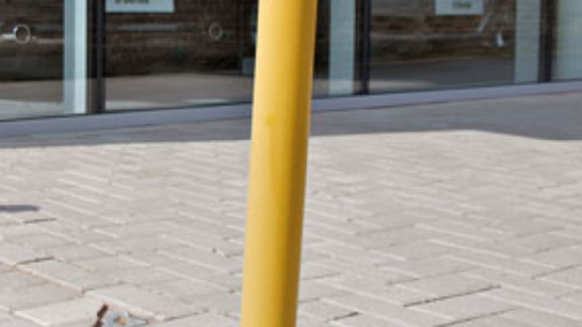 yellow fold down bollard in pavement