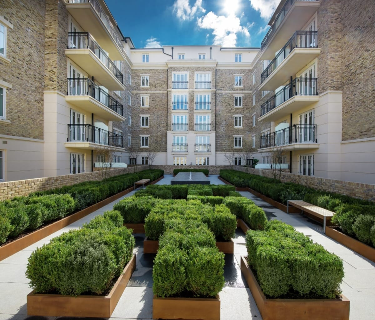 Apartments with cast stone detailing overlooking a landscaped garden