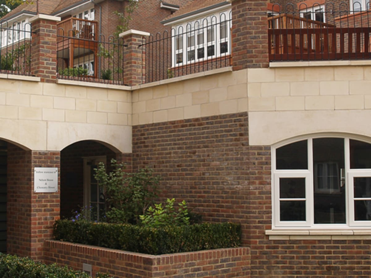 Bespoke ashlar stone walling is complemented by cast stone archways