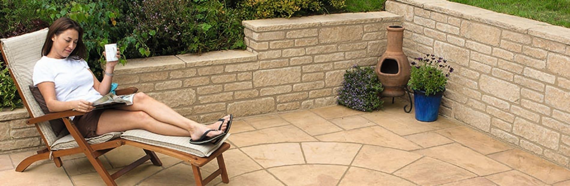 a woman reading a magazine in a garden.
