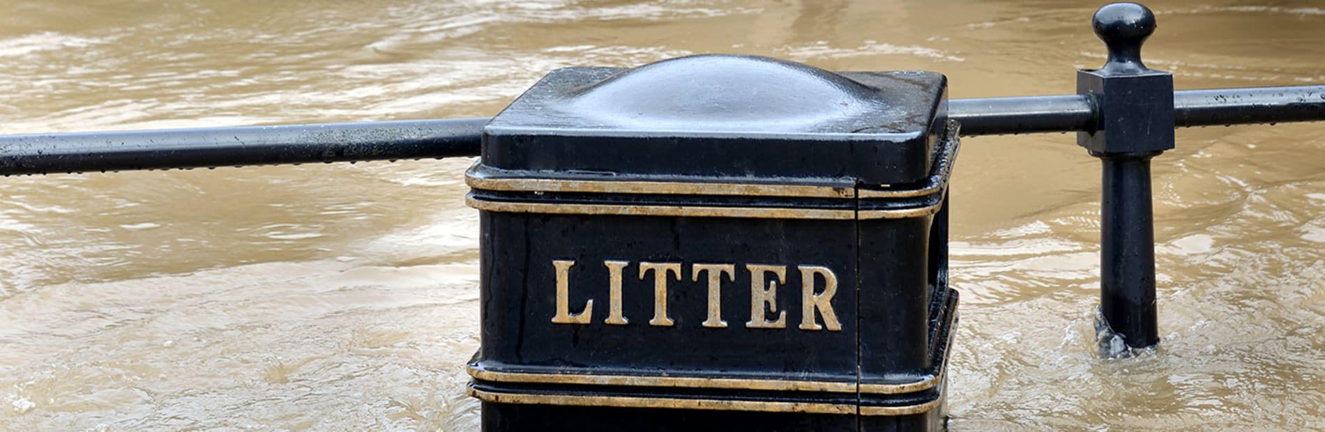A litter bin surrounded with flood waters, the water rising above the litter sign.