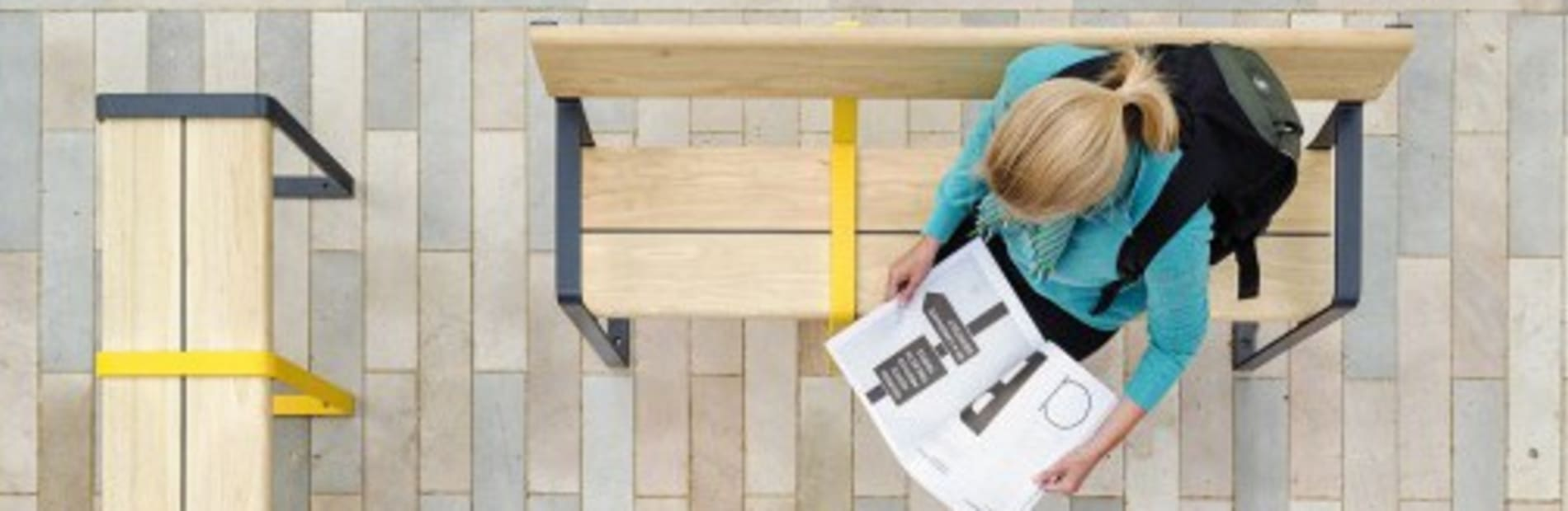 A woman sat on a wooden bench reading a brochure. The bench is a square with natural stone paving.