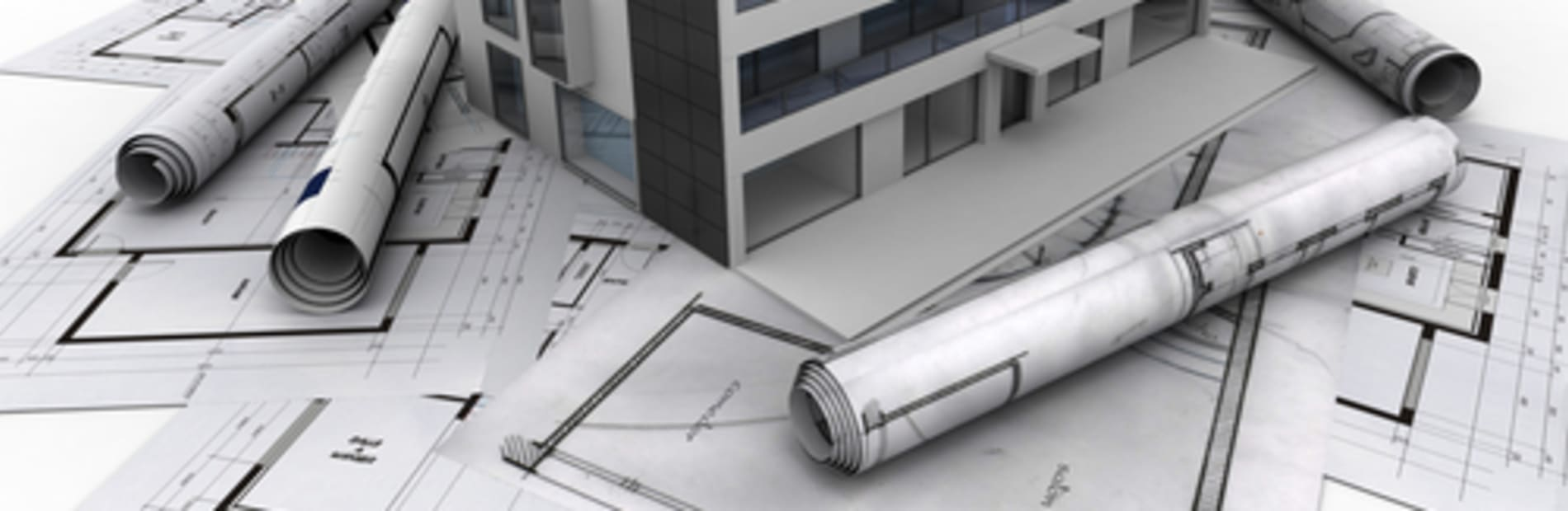 A paper building coming out of an architects drawing, surrounded by other designs and blueprints.