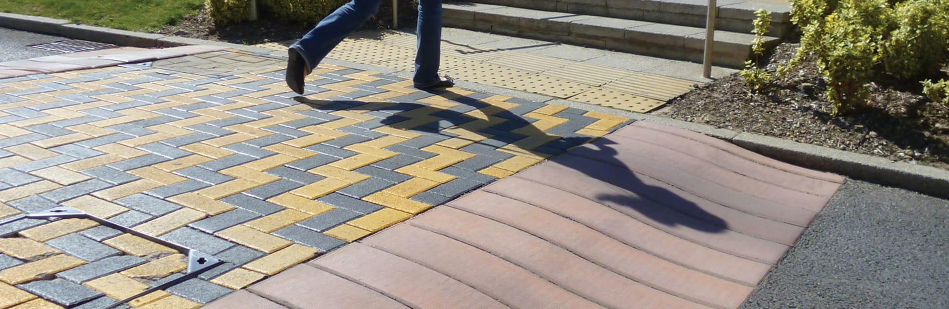 A woman walking across the S ramp reinforced concrete ramp system.
