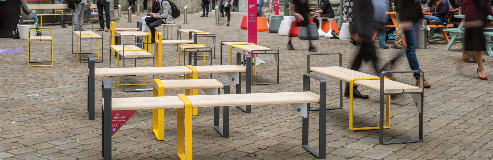 Members of the public sitting on and waling around temporary street furniture benches