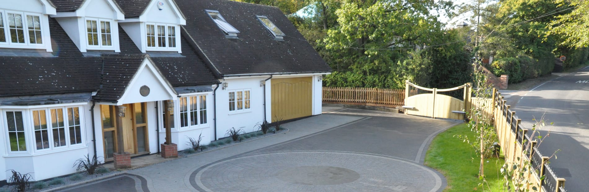A large circular driveway design using grey paving