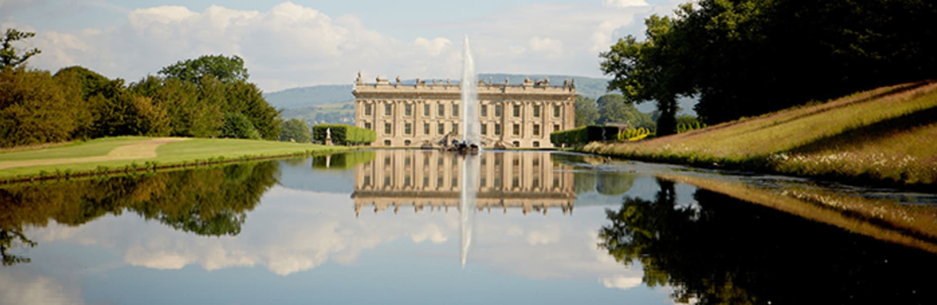 chatsworth house overlooking a lake.