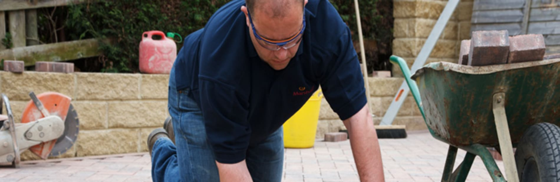 an installer laying block paving in a garden patio area.