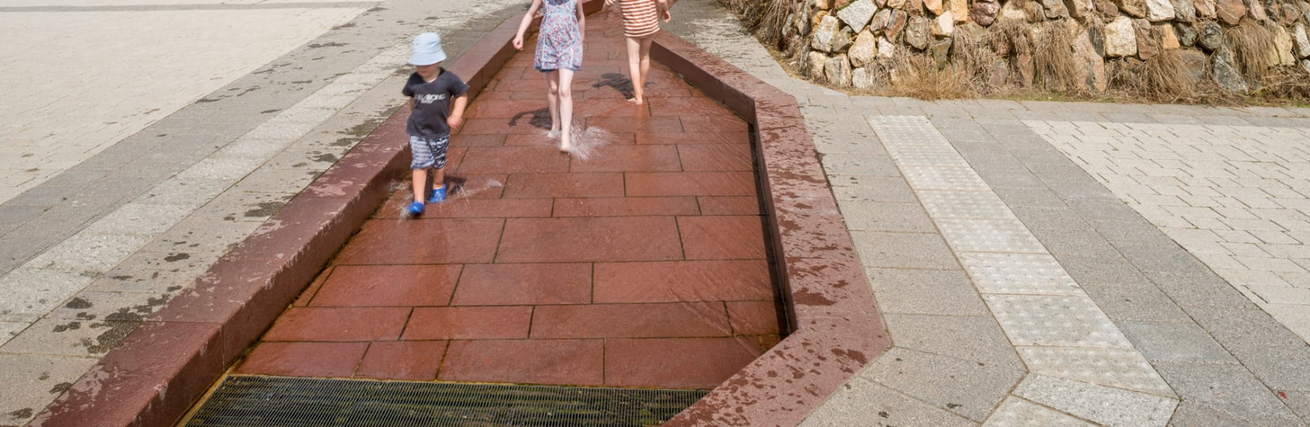 imperial red Porphyry in a water feature, children playing