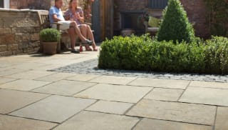 Marshalls Limestone Aluri in Rustic Ochre Multi laid in a garden patio area.
