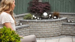 marshallite walling in rustic finish and ash multi colour used as raised bed planter with woman looking at the water feature