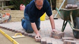 an installer laying block paving in a garden patio area.