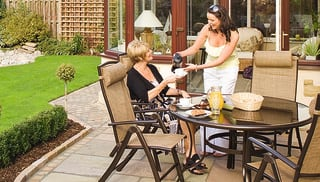 two women enjoying drinks in a garden