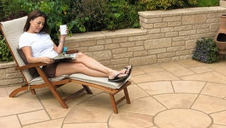 a woman reading a magazine in a garden.