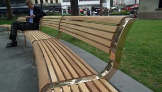 Man sat on wooden bench with bespoke bronze legs and detailing