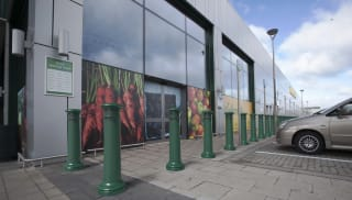 Green PAS 170 bollards outside a Morrisons store