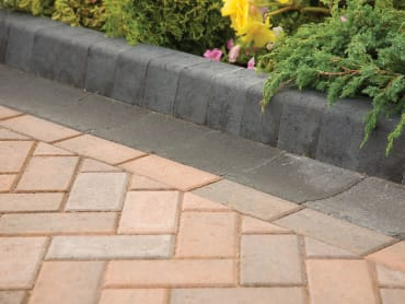 marshalls keykerb in Charcoal next to red block paving on a driveway