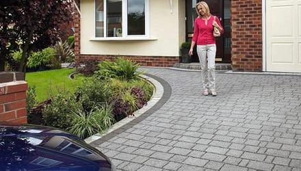 a woman walking down her driveway
