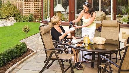 two women enjoying drinks in a garden