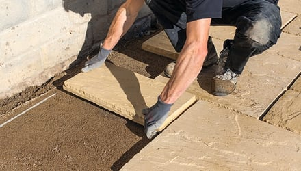 installer laying paving in a patio area