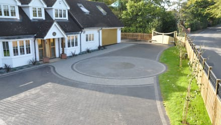 A large circular driveway design using grey paving