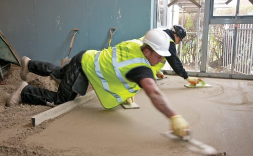 builder laying mortar on housing floor