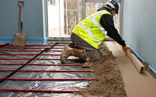 builder laying screed on housing floor.