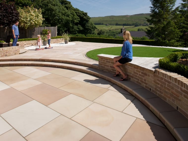 marshalls sawn versuro kingsize in autumn bronze multi set in a garden with steps and a circular grass area with family playing.