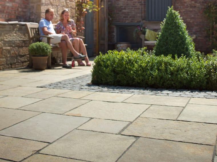 Marshalls Limestone Aluri in Rustic Ochre Multi laid in a garden patio area.