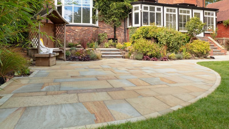Natural stone patio outside red brick home