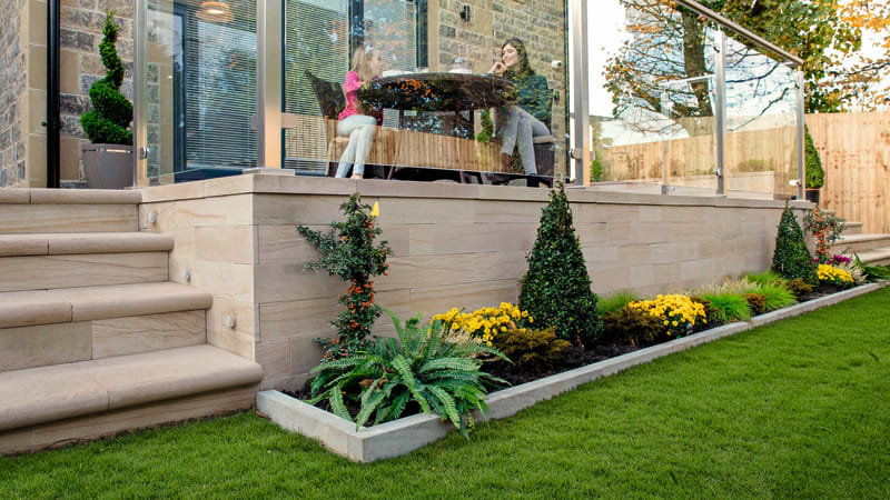 Marshalls Sawn Versuro walling in Caramel Cream in a garden with glass ballustrades and two women talking at a table