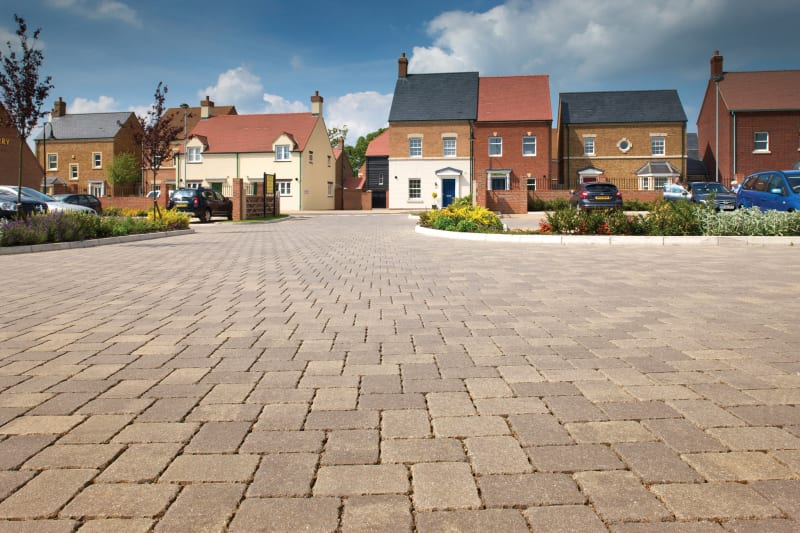 Buff block paving used in the road in front of modern housing.