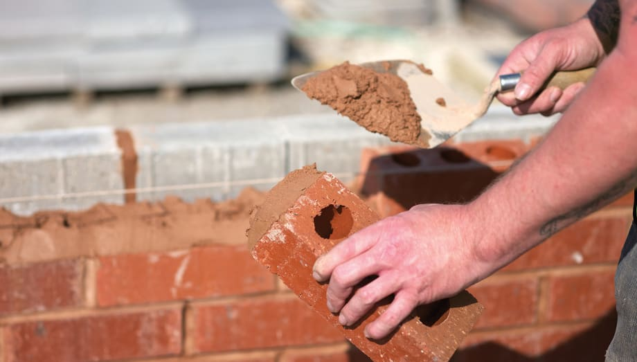 man laying a brick wall with mortar