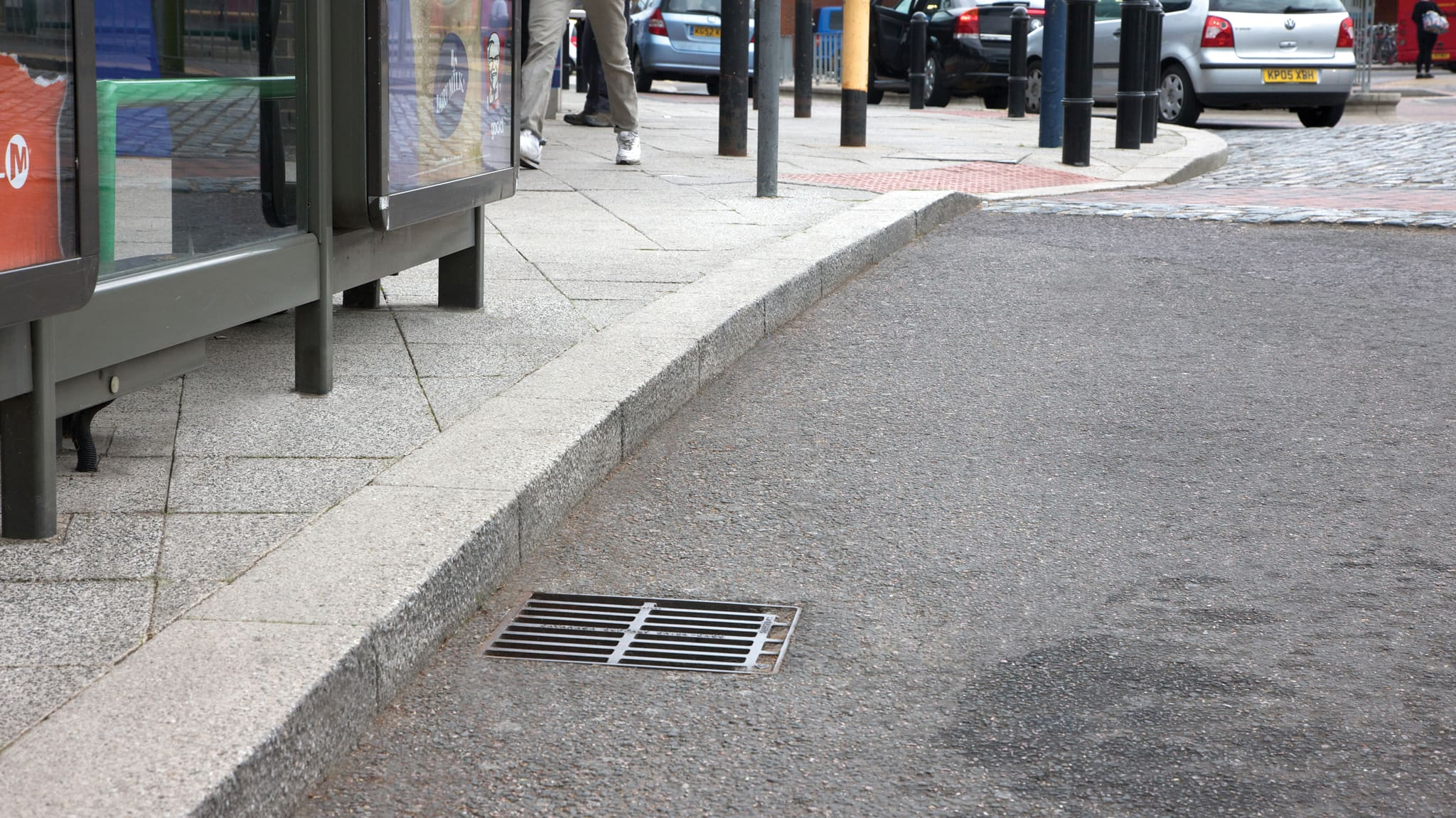 Grey conservation kerb next to a bus stop.