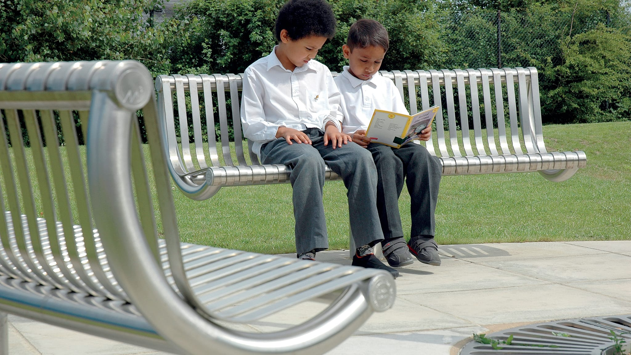 steel M3 bench with children sat reading a book