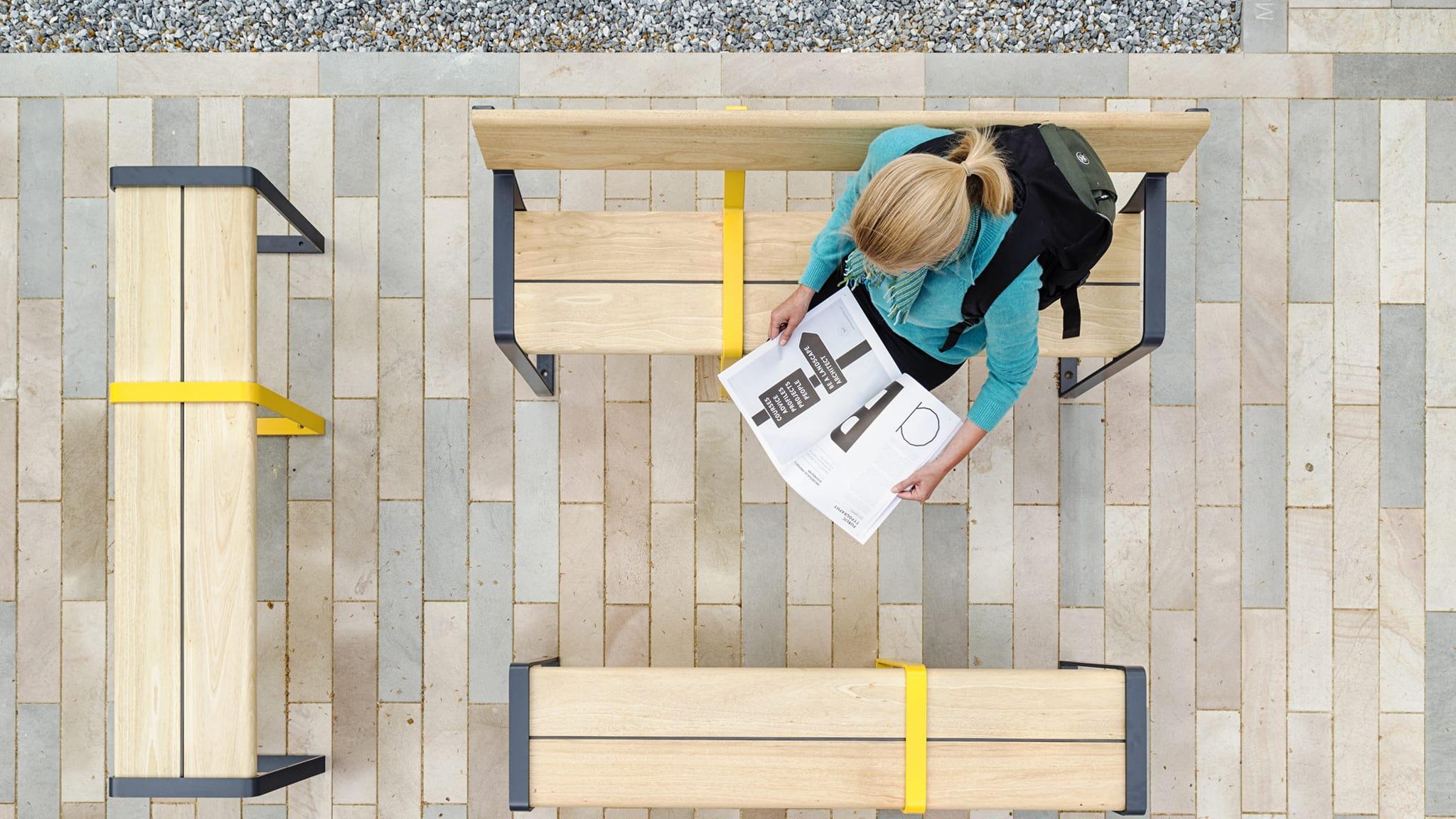 Woman reading magazine on bench
