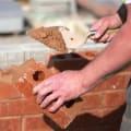 man laying a brick wall with mortar