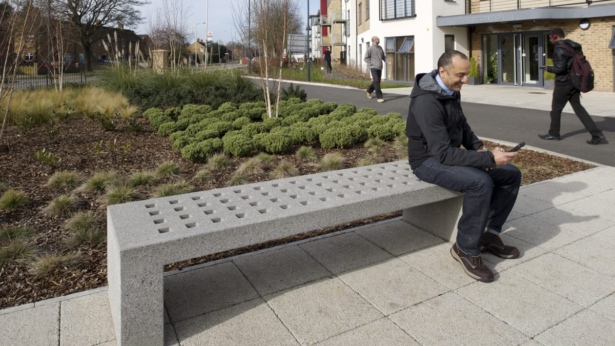 man sat on grey mayo bench outside