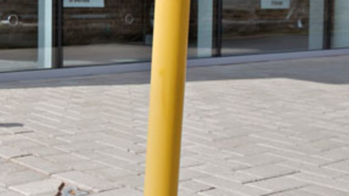 yellow fold down bollard in pavement
