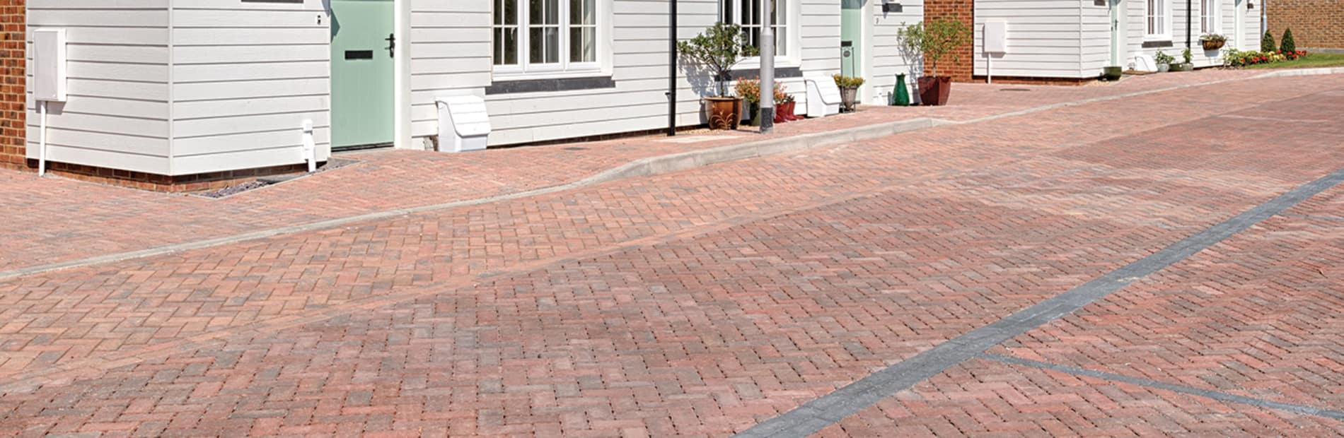 Red block paving in front of white house.