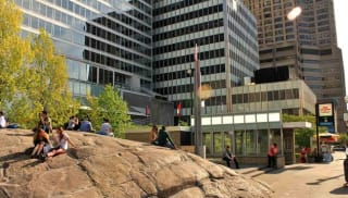People socialising a top a large rock infront of a modern urban landscape.