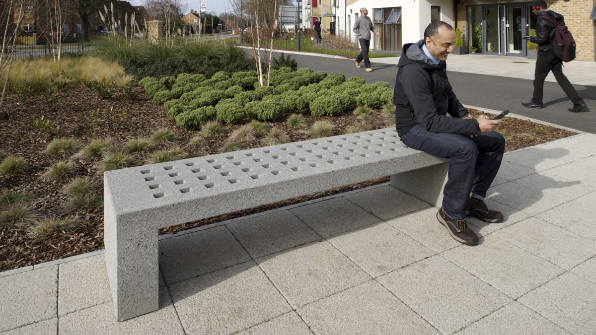 man sat on grey mayo bench outside