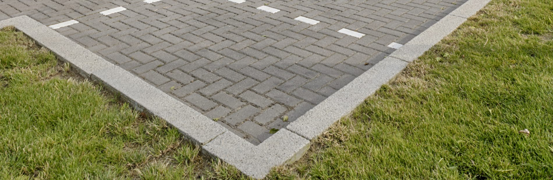 Light grey kerb used in car park in front of office building.