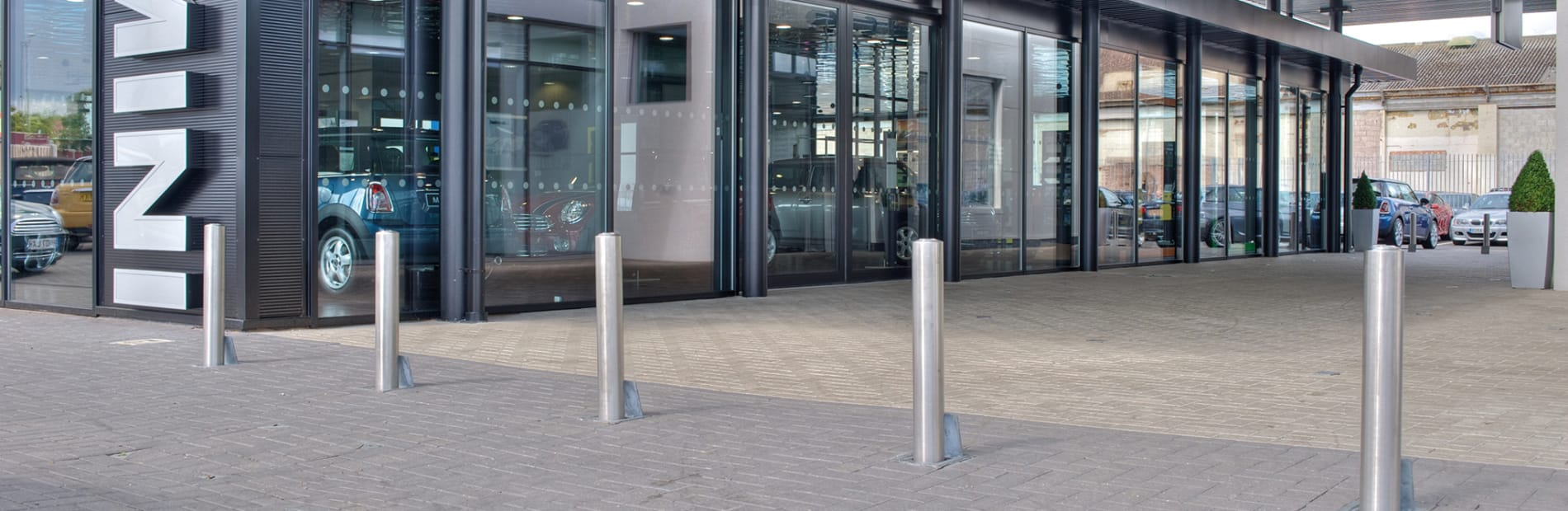 Silver bollards placed in front of a car dealership.