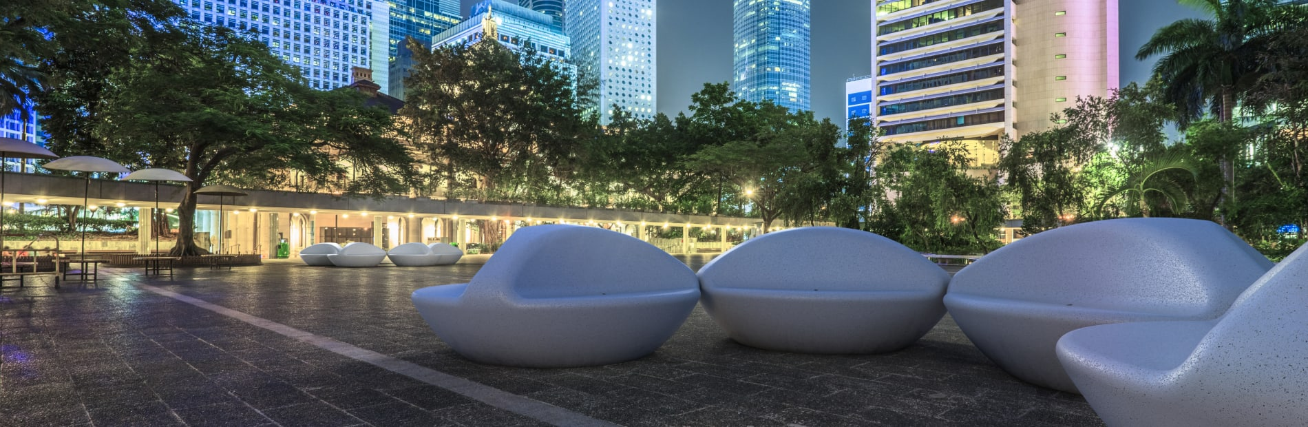 Universo benches seen at night against a city backdrop