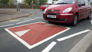 speed cushion in the road with a red car going over